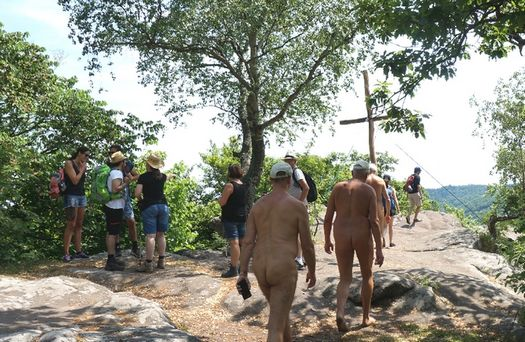 Nude and clothed togetherness at a summit cross